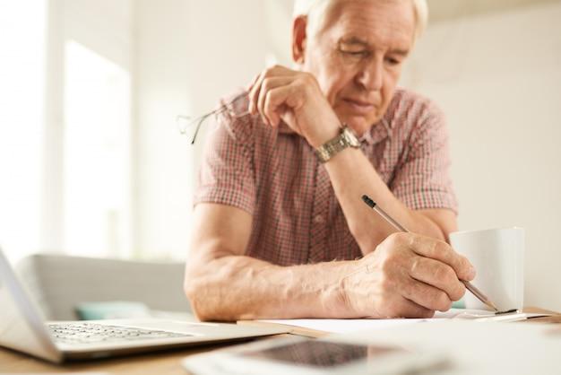 Starszy mężczyzna pisze w domu