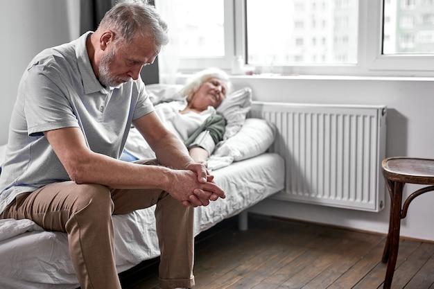 Starszy mężczyzna płaczący i opłakujący stratę swojej żony, siedzący obok niej. koronawirus, koncepcja covid-19