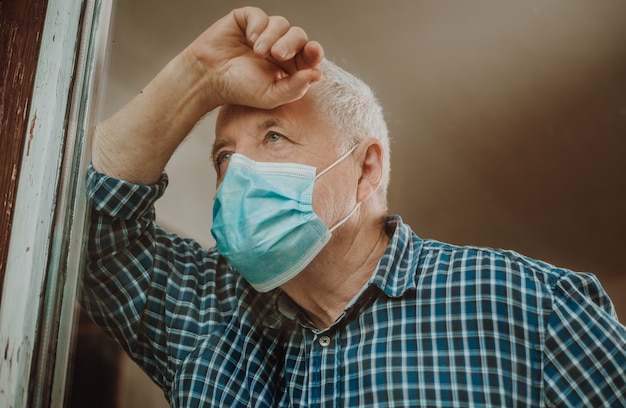 Starszy mężczyzna poddany kwarantannie przez koronawirusa, covid-2019 w domu, wyglądający na zewnątrz przy oknie