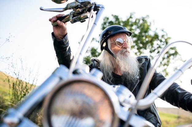 Starszy mężczyzna podróżnik z motocyklem i okularami przeciwsłonecznymi na wsi.