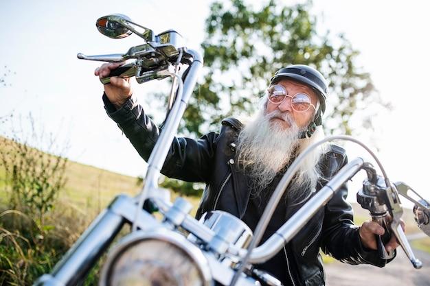 Starszy mężczyzna podróżnik z motocyklem i okularami przeciwsłonecznymi w okolicy, patrząc na kamery.