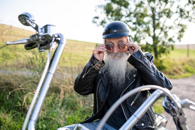 Starszy mężczyzna podróżnik z motocyklem na wsi, zakładanie okularów przeciwsłonecznych.