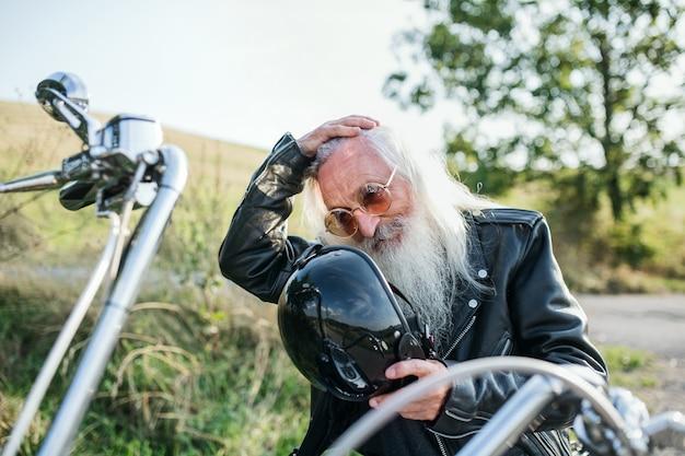 Starszy mężczyzna podróżnik z motocyklem w okolicy, odpoczynek.