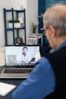 Starszy mężczyzna pokazuje butelkę pigułek do lekarza podczas korzystania z laptopa dla telemedycyny. starszy mężczyzna rozmawiający z lekarzem w trakcie rozmowy zdalnej i żoną czyta książkę na kanapie.