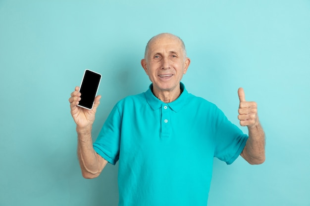 Starszy mężczyzna pokazuje pusty ekran telefonu