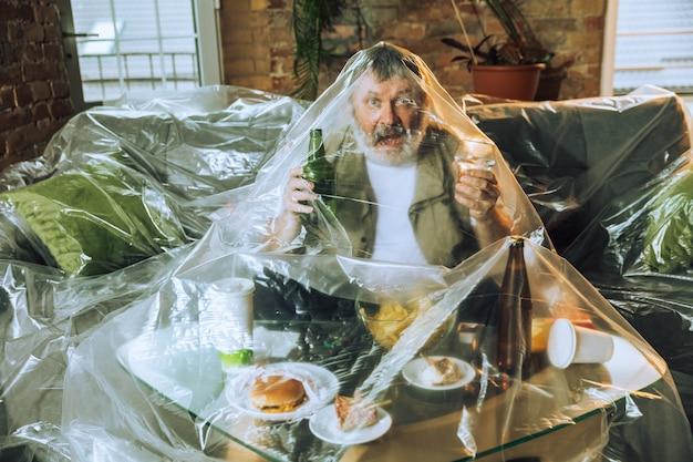 Starszy Mężczyzna Pokryty Plastikiem, Jedzenie Fast Food - Zanieczyszczenie środowiska Przez Pojęcie Ludzi. Kampania Ekologiczna. Zanieczyściliśmy Planetę Tak Bardzo, że Już Tego Nie Zauważamy. Niezdrowy, śmieci, Problem. Premium Zdjęcia