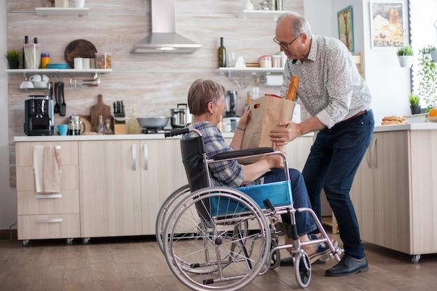Starszy mężczyzna pomaga żonie, biorąc od niej papierową torbę spożywczą. dojrzali ludzie ze świeżymi warzywami z targu. życie z osobą niepełnosprawną z niepełnosprawnością ruchową
