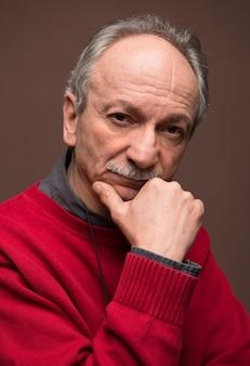Starszy mężczyzna poważny pozowanie w studio na brązowym tle