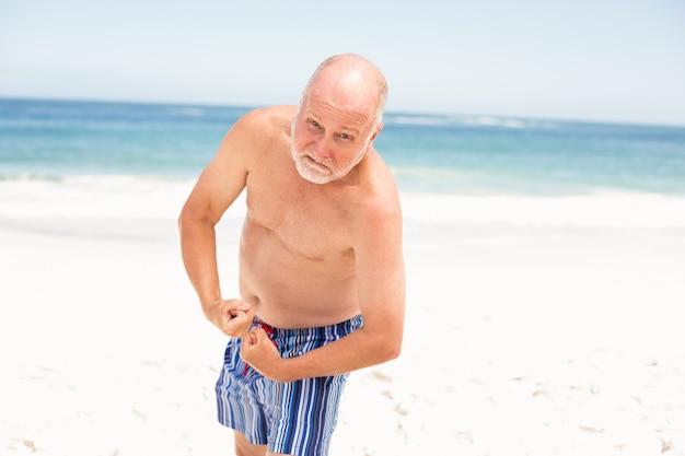 Starszy mężczyzna pozuje z jego mięśniami