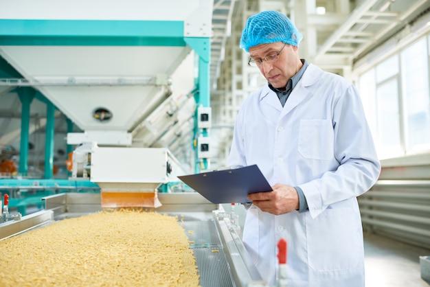 Starszy mężczyzna pracujący w fabryce żywności