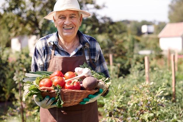 Starszy mężczyzna pracujący w polu z skrzynią warzyw