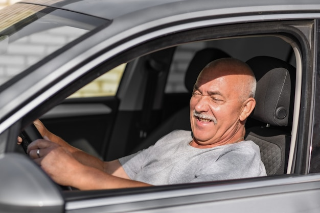 Starszy mężczyzna prowadzący samochód, patrząc w kamerę.