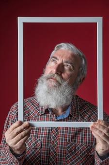 Starszy mężczyzna przyglądający up trzymający białą granicy ramę przed jego twarzą przeciw czerwonemu tłu
