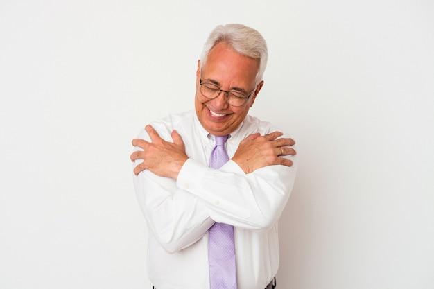 Starszy mężczyzna przytula się, uśmiechając się beztrosko i szczęśliwie.