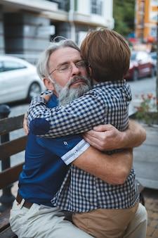Starszy mężczyzna przytulanie swojego wnuka uśmiechając się z zamkniętymi oczami