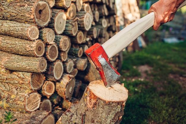 Starszy mężczyzna rąbanie drewna opałowego z siekierą w ogrodzie wsi