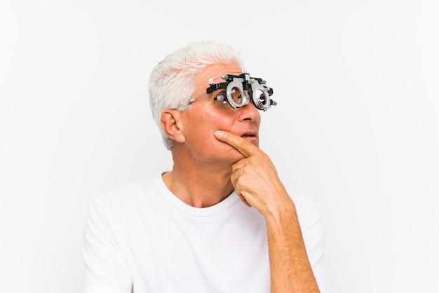 Starszy mężczyzna rasy kaukaskiej noszący ramę próby optometrysty, patrzył w bok z wyrazem wątpliwości i sceptycyzmu.