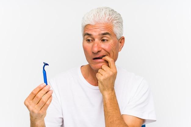Starszy mężczyzna rasy kaukaskiej trzymający żyletkę na białym tle 㧠gryzące paznokcie, nerwowy i bardzo niespokojny.
