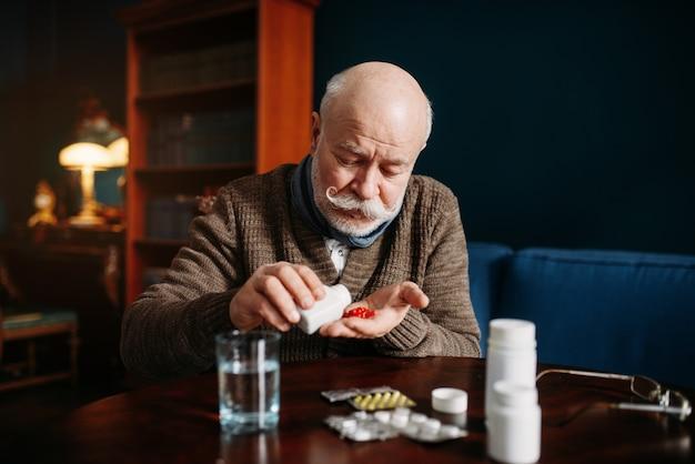Starszy mężczyzna ręka z pigułkami, choroby związane z wiekiem