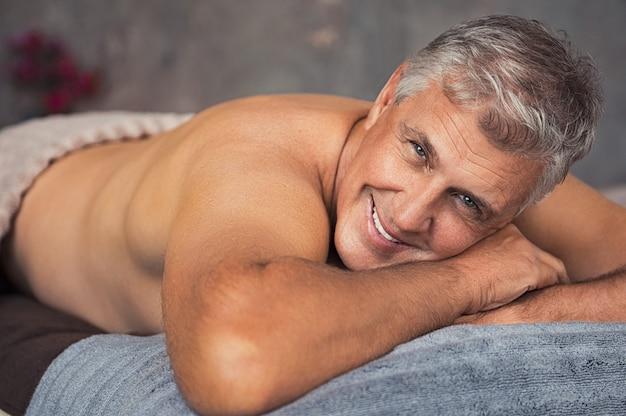 Starszy mężczyzna relaksuje przy zdrojem