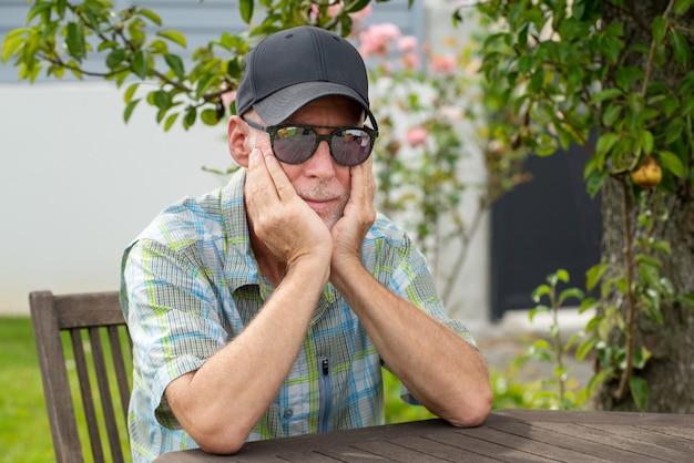 Starszy mężczyzna relaksuje w ogródzie w baseball nakrętce z okularami przeciwsłonecznymi