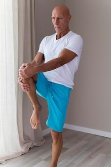 Starszy mężczyzna robi ćwiczenia rozciągające