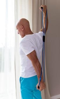 Starszy mężczyzna robi ćwiczenia w domu