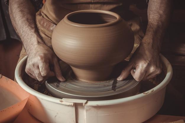 Starszy mężczyzna robi garnkowi używać ceramicznego koło