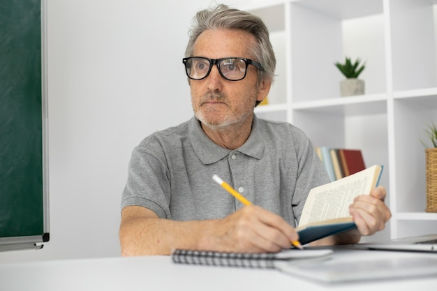Starszy mężczyzna robi notatki w klasie