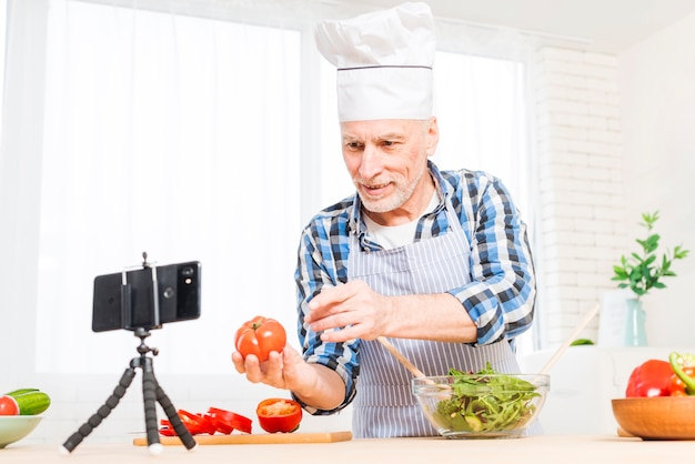 Starszy mężczyzna robi wideo wezwaniu na telefonie komórkowym pokazuje heirloom pomidoru podczas przygotowywać sałatki