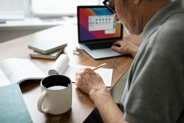 Starszy mężczyzna robi zajęcia online na laptopie w domu