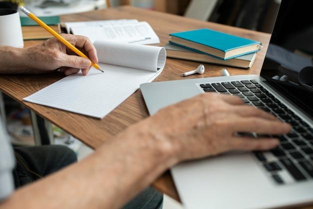 Starszy mężczyzna robi zajęcia online na laptopie