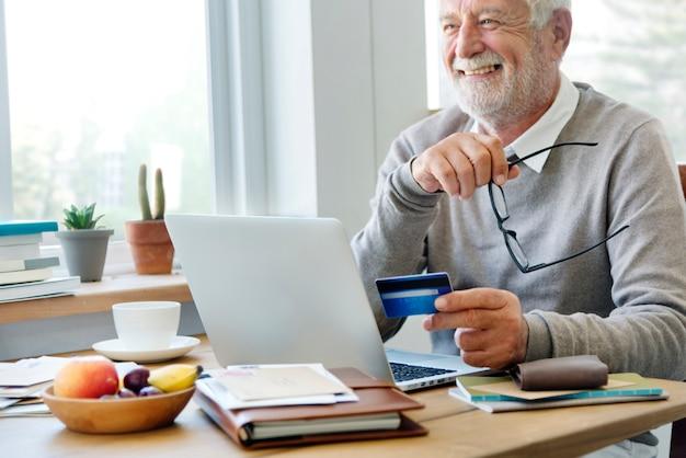 Starszy mężczyzna robi zakupy online z kredytową kartą