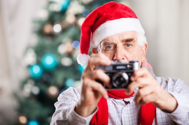 Starszy mężczyzna robienie zdjęć na tle bożego narodzenia