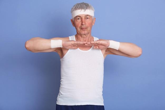 Starszy mężczyzna rozciągający ręce w pomieszczeniu, rozgrzewający się przed treningiem lub grą w tenisa, dojrzały mężczyzna ubrany w białą koszulkę, opaskę na włosy i nadgarstek.