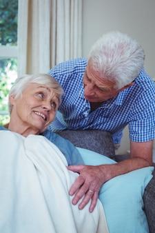 Starszy mężczyzna rozmawia z chorą żoną
