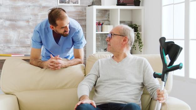 Starszy mężczyzna rozmawia z pielęgniarzem w przytulnym domu opieki.