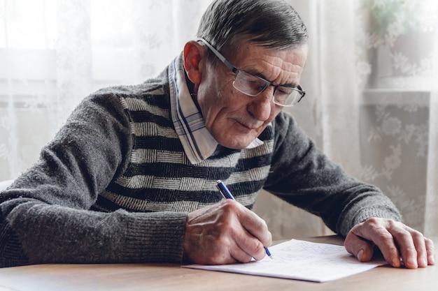 Starszy mężczyzna rozwiązuje sudoku lub krzyżówkę