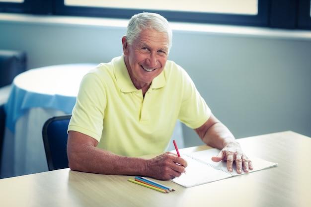Starszy mężczyzna rysunek ołówkiem w rysunek książki