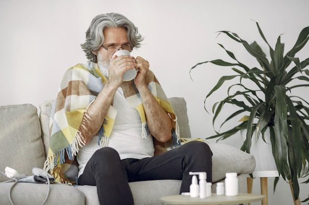 Starszy mężczyzna sam siedzi na kanapie. chory mężczyzna pokryty kratą. grangfather z filiżanką herbaty.