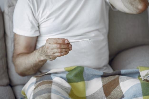 Starszy mężczyzna sam siedzi na kanapie. chory mężczyzna pokryty kratą. grangfather z termometrem.