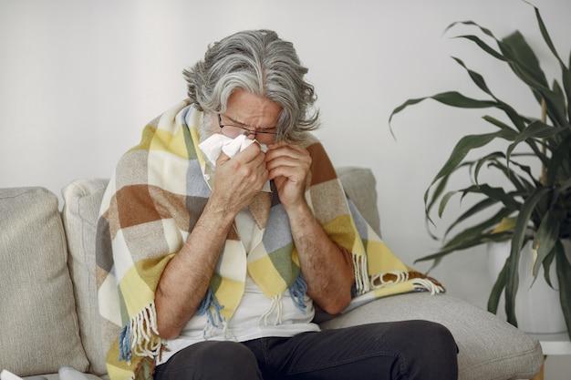 Starszy mężczyzna sam siedzi na kanapie. chory mężczyzna pokryty kratą.
