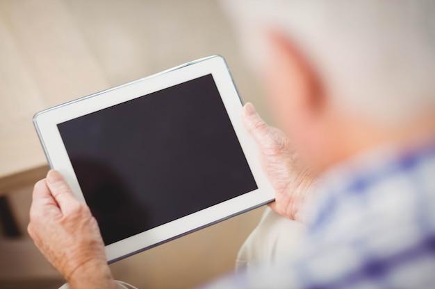 Starszy mężczyzna siedzi na kanapie i za pomocą cyfrowego tabletu w salonie