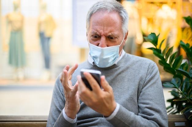 Starszy mężczyzna siedzi na ławce i używa smartfona w centrum handlowym w masce i złości się, koncepcja koronawirusa