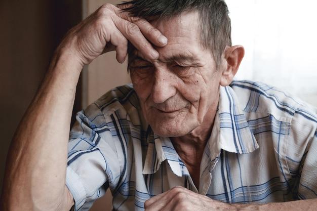 Starszy mężczyzna siedzi trzymając się za głowę, cierpi na utratę pamięci