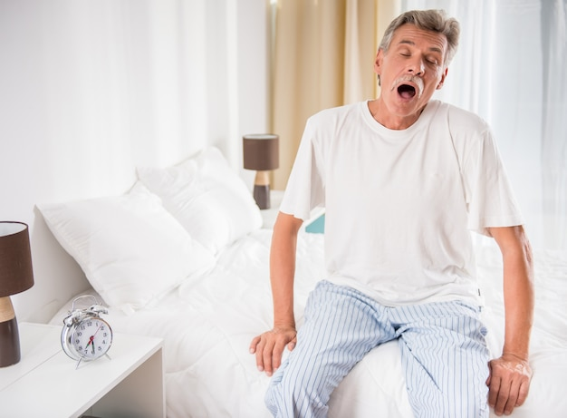 Starszy mężczyzna siedzi w łóżku i ziewa.