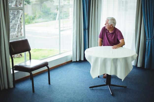 Starszy mężczyzna siedzi w salonie