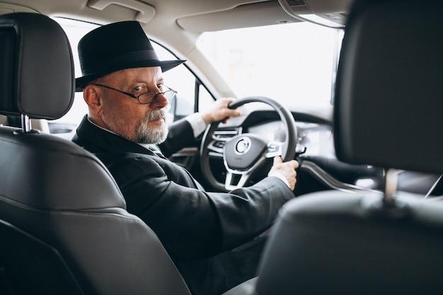 Starszy mężczyzna siedzi w samochodzie
