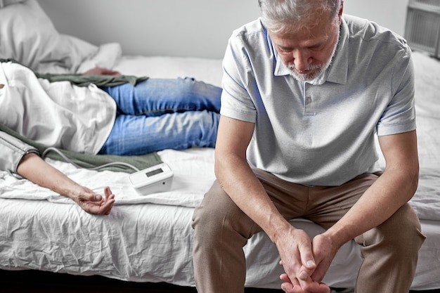 Starszy mężczyzna siedzi z chorą żoną leżąc na łóżku, źle się czuje, kobieta jest u progu śmierci, mężczyzna bardzo się o nią martwi