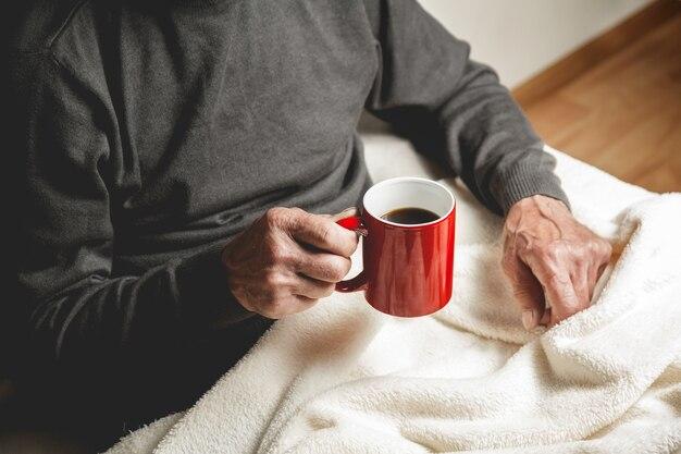Starszy mężczyzna siedzi z filiżanką kawy w ręku